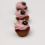 Schokocupcake mit Schokoganache und Buttercremeröschen, garniert mit einer Heidelbeere